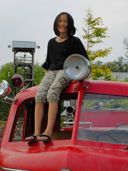 Claire sitting on the fire truck cab at Remlinger Farms.